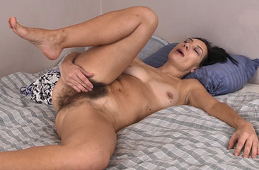 Eva is a mature brunette with a petite figure, small breasts and a hairy pussy.  She gets the urge to play with herself while laying in bed in her comfortable pajamas, so she slowly strips and begins to slowly rub her clit as her hips start to move to the same rhythm.