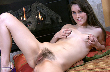 Cute pale vixen Michelle L shows off her remarkable tight body by the fireplace. When shes warm, her hands begin to wander down to her moist hairy pussy.
